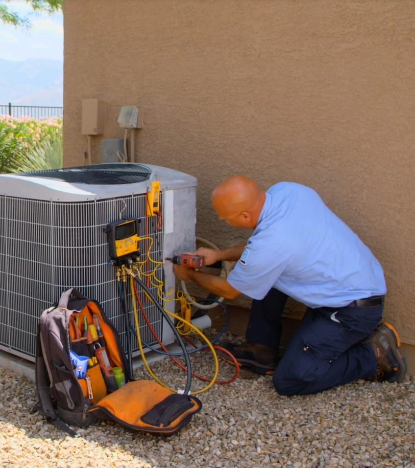 D&H AC - Myle HVAC Technician repairing an AC unit in a home in Tucson