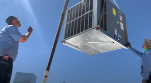 Air Conditioning installation: AC lowered on roof by a crane boom