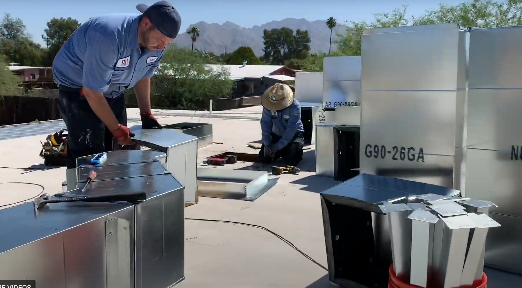 2 HVAC technicians proceeding with an air conditioning installation on a roof in Casas Adobes
